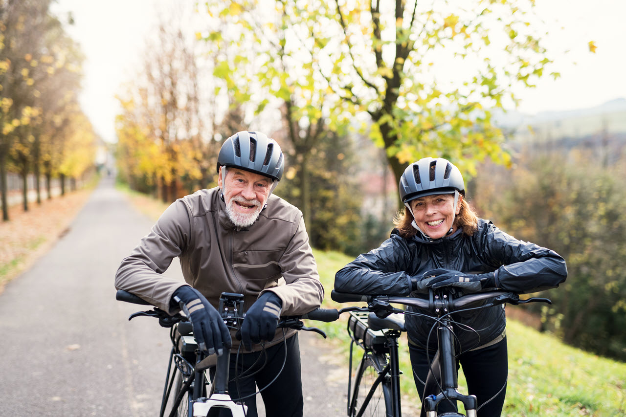 active-senior-couple-with-electrobikes-standing-ou-F9LNTK7