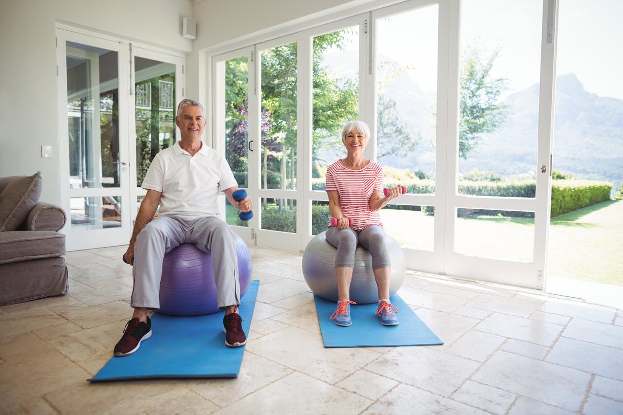 senior-couple-exercising-with-dumbbells-on-exercis-9N6ERWU